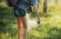 woman applying bug spray while on a hike