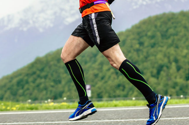 man running while wearing compression socks