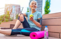 elderly woman eats apple after yoga workout