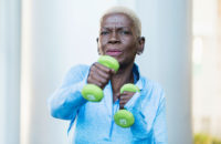 elderly woman uses weights for resistance training