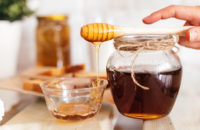 honey dripping from honey dipper which is resting on jar of honey