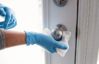 disinfecting wipes being used to clean doorknob