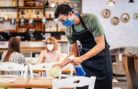 server wiping down tables in restaurant while wearing mask and face shield