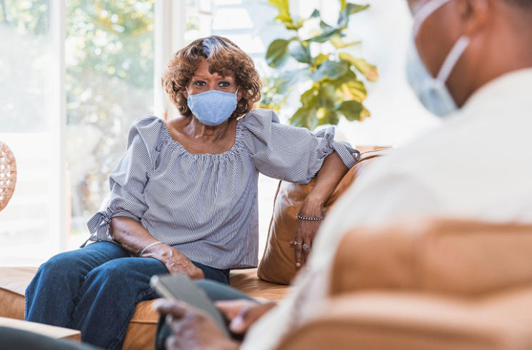 elderly woman masking at home with son