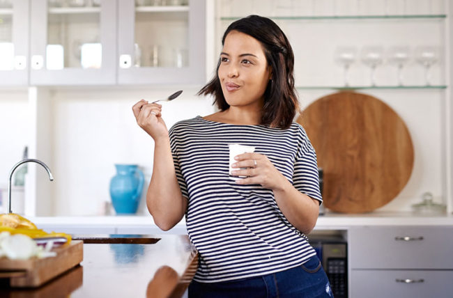 woman eating yogurt while standing in kitchen