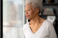 older woman sad looking out window