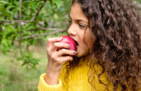 girl taking a bite of an apple