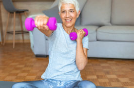 elderly woman lifts weights at home