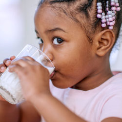 young girl drinks milk