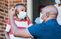 parent putting covid face mask on child