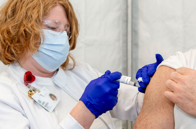 Nurse givng a covid vaccine to patient