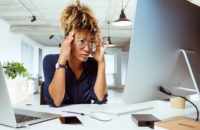 woman with headache while working with computer