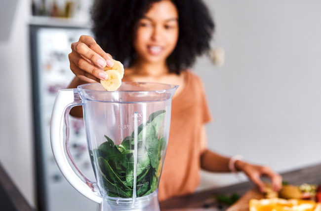 woman making a smoothie that includes bananas and spinach