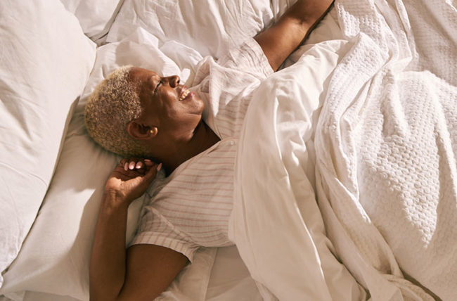 woman waking up in morning after refreshing sleep