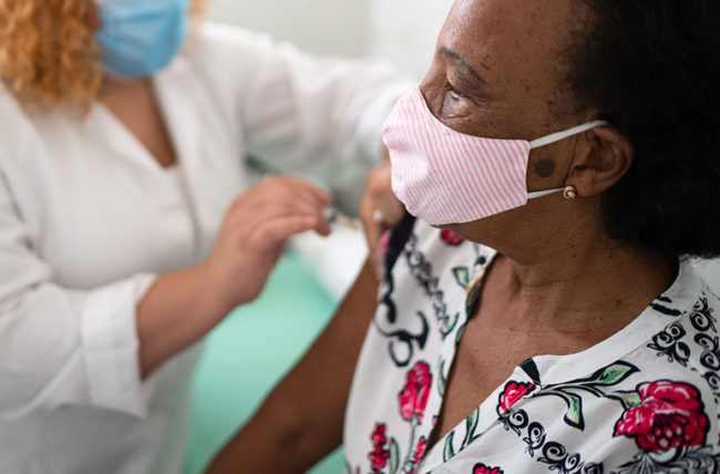 woman getting vaccinated while wearing a mask