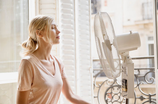 young lady sitting in front of standing fan to cool down