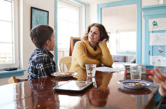 mother having serious conversation with son at kitchen table