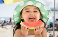 happy girl eating watermelon at the beach
