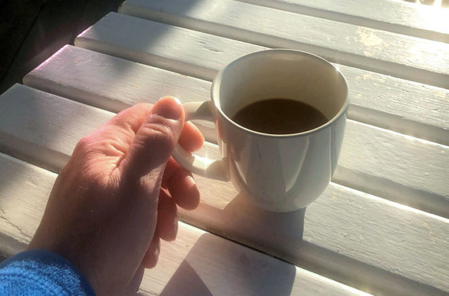 Man drinking coffee on deck in morning