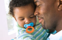 baby with pacifier held by daddy