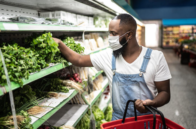 man picking lettuce from shelf at grocery store during pandemic