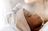 woman with hair towel at spa steaming her face