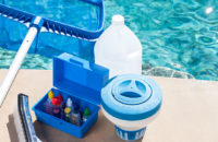 pool chemicals and testing kit sitting next to a pool
