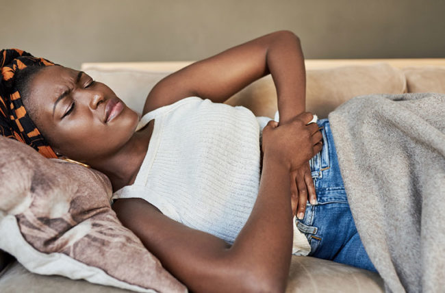 woman on couch in pain colon cancer