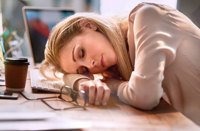 woman asleep at her desk during the day