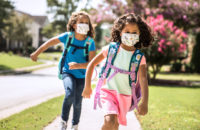 covid masked children with backpacks running home from school